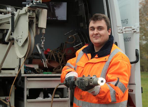 Mit der Spezialkamera, die Tjark Boos in Händen hält,  kann er die unterirdischen Leitungen auf Schäden inspizieren. Das Echtzeitbild wird  auf den Monitor im Fahrzeug übertragen.