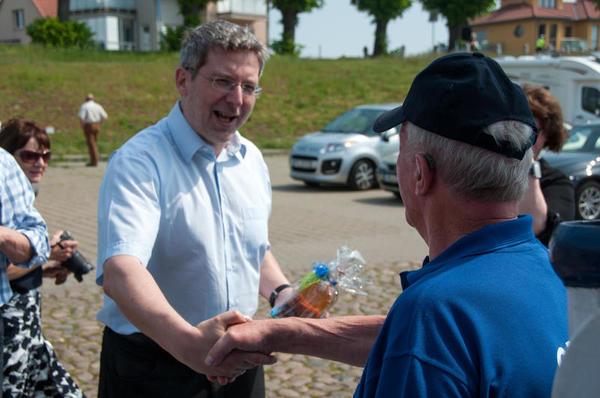 Bürgermeister Dr. Oliver Hermann begüßt Kapitän Günther Holtz mit einer Flache Fährmann.